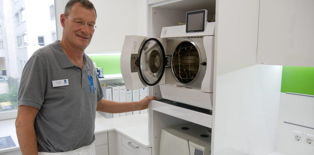 Zahnarzt Henrik Putze in seiner Praxis in Stuttgart. Er zeigt die Geräte, in denen die Instrumente sterilisiert werden. Foto: Uwe Roth